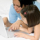 Woman and girl using laptop computer on bed, close-up