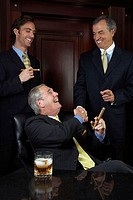 Three businessmen celebrating with cigars