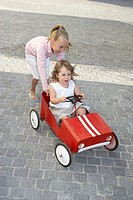 Sister pushing her younger sister in a toy car (thumbnail)