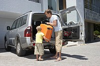 Son helping his father pack the car