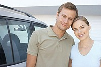 Mid adult couple stood outside with car