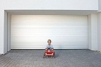 Young boy sat in a toy car