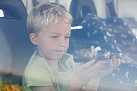 Boy sat in car holding toy car