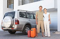 Couple stood by car with suitcases