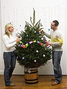 Mid adult couple decorating christmas tree