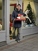 Man carrying gifts out of shop