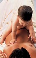 Baby boy sitting on mother´s stomach, elevated view