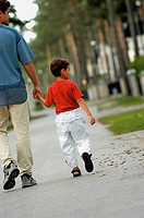 Rear view of a father and his son walking on the road