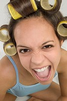 Young woman in curlers making a face