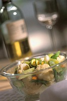 Mixed vegetables in a bowl with wineglass behind it, close-up, selective focus