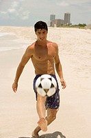 Young man playing with a soccer ball on the beach