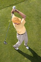 High angle view of a young man swinging a golf club