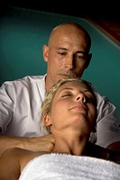 Close-up of a young woman getting a massage from a massage therapist