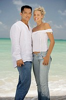 Portrait of a young woman and a mid adult man smiling on the beach