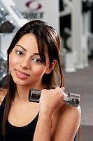 Portrait of a young woman holding a dumbbell