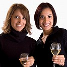 Portrait of two young women holding glasses of wine