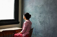 Young woman sitting at old school desk with blackboard behind her and the words 'back to school' on board