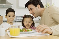 Man and two children sitting at table in kitchen, close-up