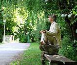 Man sitting on park bench, meditating