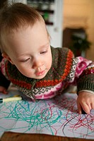 Little boy doodling with wax crayons