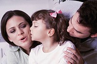 Couple and daughter kissing each other, close-up