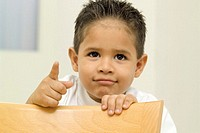 Young boy leaning on chair and pointing