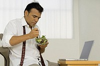 A man eating salad from a bowl