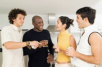 Four friends in a kitchen with drinks