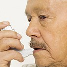 Senior man using inhaler, close-up