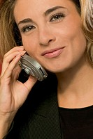 Businesswoman in black suit using a mobile phone, close-up