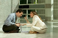 Smiling businessman and businesswoman sitting on floor face to face using laptop
