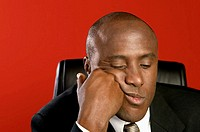 Black businessman sitting and thinking with hand against head