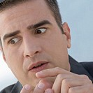 Worried businessman outdoors counting on fingers, close-up