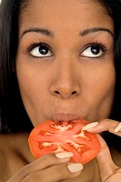 Close-up of a young woman eating a slice of tomato
