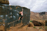 Male climber bouldering at Big Bend area near Moab, Utah, USA