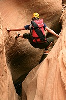 Female canyoneer stemming across a sandstone slot in Pritchett Canyon near Moab, Utah, USA
