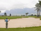 Golfer looking over sand trap