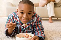 Boy lying in living room eating cereal