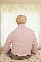 Elderly man sitting on a bed
