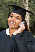 Female graduate using a cellular telephone