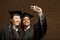 Two female graduates taking a photograph (thumbnail)
