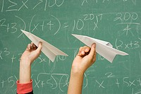 Two students about to throw paper aeroplanes