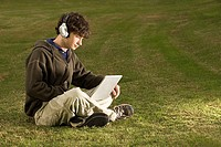 Male student using a laptop computer outdoors