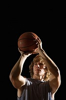 Young man aiming basketball