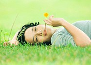 Young woman lying on grass with flower in mouth