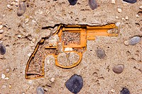 Toy gun encrusted in cement