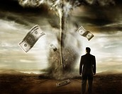 Businessman watching dollar bills flying out of a tornado