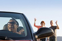Friends waving at woman driving convertible