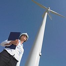 Low angle view of female engineer by wind turbine