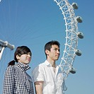 Young couple posing by Ferris wheel